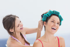 Girl fixing her friends hair rollers Stock Photo