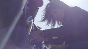 Caucasian girl fixing her motorcycle or checking condition in soft light close-up. Hobby, traveling and active lifestyle. The girl fixing her motorcycle or stock video footage