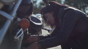 Caucasian girl fixing her motorcycle or checking condition in soft light close-up. Hobby, traveling and active lifestyle. The girl fixing her motorcycle or stock footage