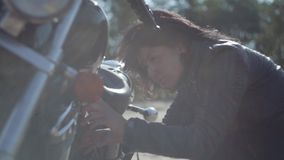 Caucasian woman fixing her motorcycle or checking condition in soft light close-up. Hobby, traveling and active. The girl fixing her motorcycle or checking stock video footage