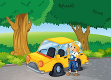 A girl fixing the yellow car near the big trees Stock Photo