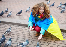 The girl with a flag feeds the pigeons on the square. KIEV, UKRAINE : Mass meeting for European Integration and the government's resignation, February 16, 2014 stock images