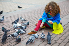 The girl with a flag feeds the pigeons on the square Stock Photography