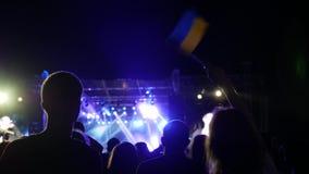 Girl with flag Ukraine at concert, beautiful ukrainian woman waving national flag, people on rock concert stock video