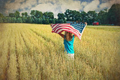 Girl with flag in wheat field