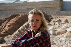 Girl in flannel shirt on the rocky beach Royalty Free Stock Photo