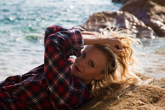 Girl in flannel shirt on the rocky beach Stock Images