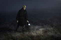 Girl with a flashlight in the field. At night looking for something Stock Photos