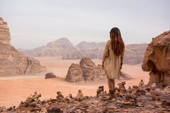 A girl in a flesh dress stands among the pyramids of desires, the pyramids of stones. In the background a desert landscape