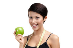 Girl with flexible ruler and green apple Stock Images