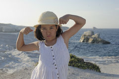Girl flexing muscles on beach Royalty Free Stock Photos