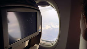 Girl flies in an airplane and admires the scenery in the porthole and closes it. stock video