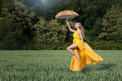 Girl flies over the field. In his hand umbrella. stock photography