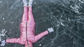 Girl flies and rolls on the ice. Young couple has fun during winter walk against background of ice of frozen lake. Lovers lie on clear ice with cracks, have stock video footage