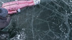 Girl flies and rolls on the ice. Young couple has fun during winter walk against background of ice of frozen lake. Lovers lie on clear ice with cracks, have stock footage