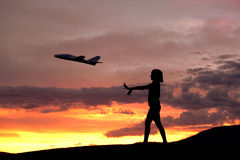 Girl flies a toy plane. Stock Photography