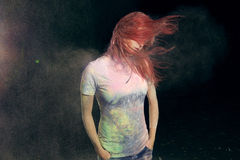 Girl Flinging Red Hair. Redhead girl with colored powder trailing behind her hair that she is flinging up Royalty Free Stock Image