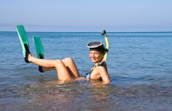 Girl in in the sea. Girl in flippers and mask lies in the sea Royalty Free Stock Photos