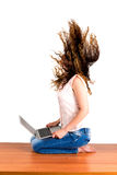 Girl flipping hair holds the laptop. Young woman holds the laptop flipping hair sitting on a table Stock Photos
