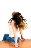 Girl flipping hair sitting on a white background Stock Images