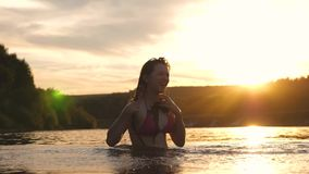 Girl flips back hair. beautiful spray of water in rays of sunset. splash of water. playful girl splashes her long hair. In a refreshing summer evening near stock video
