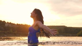 Girl flips back hair. beautiful spray of water in rays of sunset, a splash of water in rays of the sun. she sprinkles stock video footage