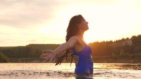 Girl flips back hair. beautiful spray of water in rays of sunset, a splash of water in rays of the sun. she sprinkles stock video