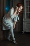 Girl flirtatiously straightens stockings on legs. Royalty Free Stock Image