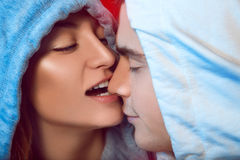 Girl flirts to her boyfriend biting his nose. In studio stock images