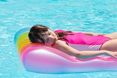 Girl floating on airbed. Young girl with her eyes closed resting on a colorful airbed in a swimming pool stock photos