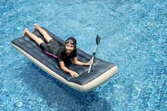 Girl on the floating bed #2. Girl enjoyed on the floating bed in the swimming pool Royalty Free Stock Images