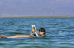 Girl floating at the Dead Sea