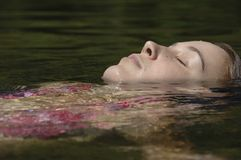 Girl floating on her back. Royalty Free Stock Photo