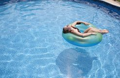 Girl floating in pool Royalty Free Stock Images