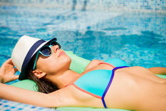 Girl floating in the  pool. Royalty Free Stock Photo
