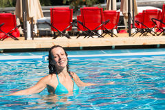 Girl floating in the pool and smiling Royalty Free Stock Image