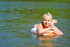 Girl floating in the river Stock Images