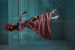Girl floating in the room. Girl hovers in the room at night. It levitates in a dream Royalty Free Stock Photography