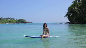 The girl is floating on a surfboard.  stock video