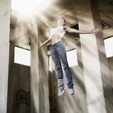 Girl floating up to bright light. Young sexy dancer girl in air rising up towards bright light on ceiling in old grungy factory hall Stock Photos
