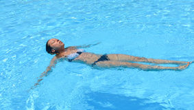 Girl floating in the water in a swimming pool Royalty Free Stock Photography