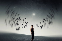 Girl and a flock of crows Royalty Free Stock Image
