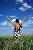 Girl in a floor. Girl costs in a floor with the hands lifted upwards, on a background of clouds in the blue sky Stock Photography