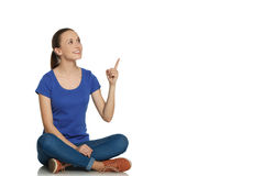 Girl on the floor and pointing finger. Stock Photography