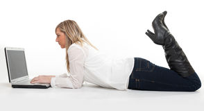 Girl on the floor using laptop profile Stock Image