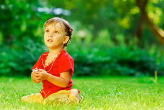 Girl with florets on a lawn. The little girl sits on a green lawn, holds flowers in hands and looks upwards Royalty Free Stock Images