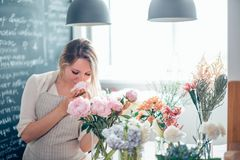 Girl florist with closed eyes smiling sniffing bouquet flowers over white wall. stock image