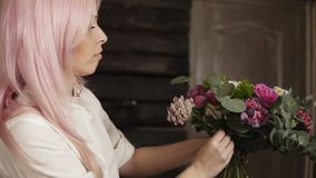 The girl florist is concentrated on a bouquet arranging. Collection of beautiful, fashionable flowers. Process.  stock footage