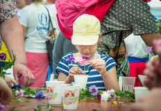 Girl at floristic workshop. Zaporizhia/Ukraine- May 28, 2017: Charity Family festival:  teen girl participating at floristic workshop, learning to arrange fresh Royalty Free Stock Photo