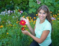 The girl with a flower. The girl shows a red flower dahlias stock photography